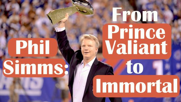 Former New York Giants quarterback Phil Simms holds up the Lombardi trophy he won as the Super Bowl XXI MVP.
